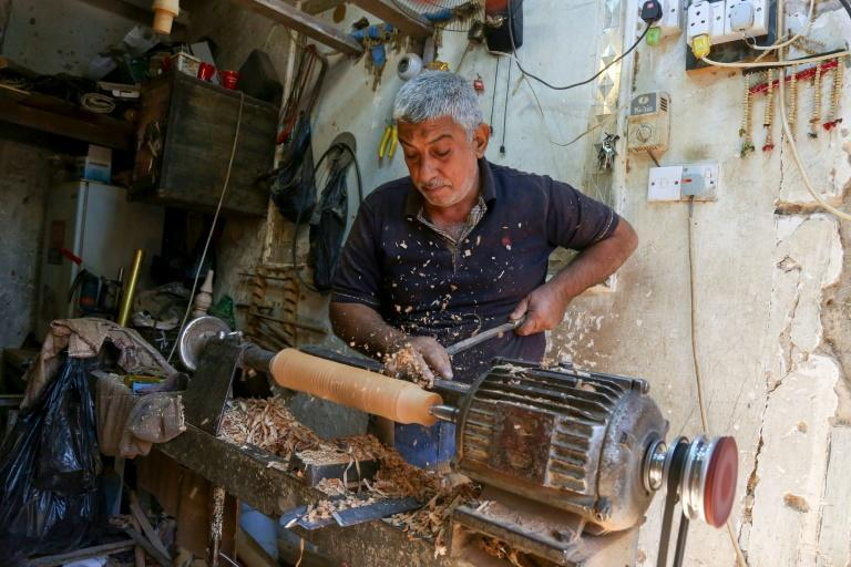 A carpenter in Karbala shaves a piece of wood to make a waterpipe at his workshop using local white willow wood