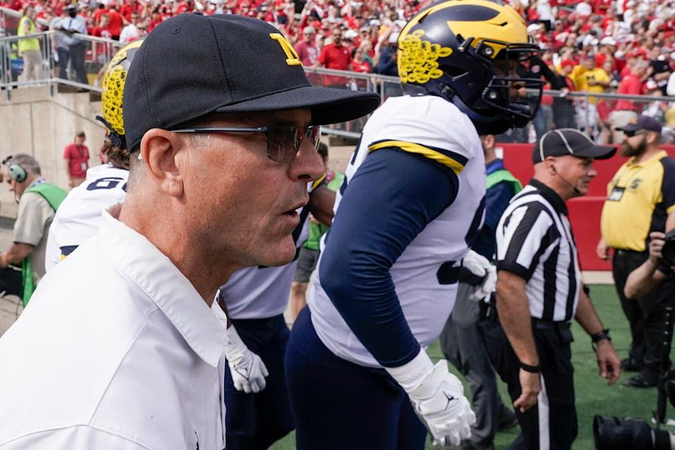 Michigan head coach Jim Harbaugh leads his team on the field before an NCAA college football game against Wisconsin Saturday, Oct. 2, 2021, in Madison, Wis.