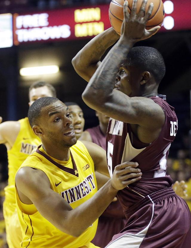 Montana's Nick Emerson, right, is defended by Minnesota's Andre Hollins in the first half of an NCAA college basketball game, Tuesday, Nov. 12, 2013, in Minneapolis. (AP Photo/Jim Mone)