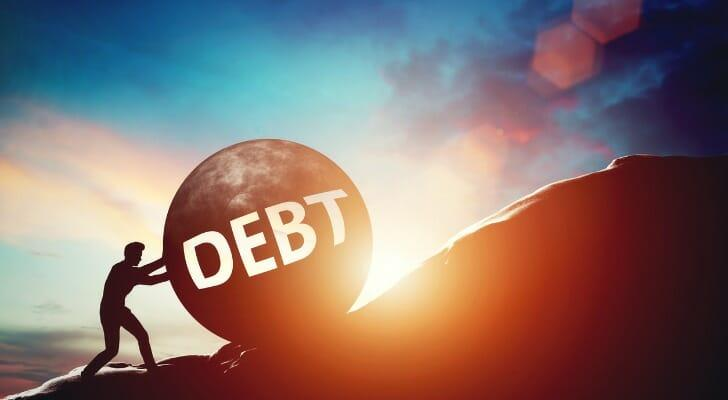 """Man pushing a large ball labeled """"DEBT"""" up a steep hill"""