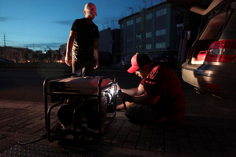 A man tries to repair a generator in San Juan, Puerto Rico