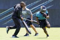 Jacksonville Jaguars running back Travis Etienne Jr., right, runs past coaches as he preforms a drill during an NFL football rookie minicamp, Saturday, May 15, 2021, in Jacksonville, Fla. (AP Photo/John Raoux)