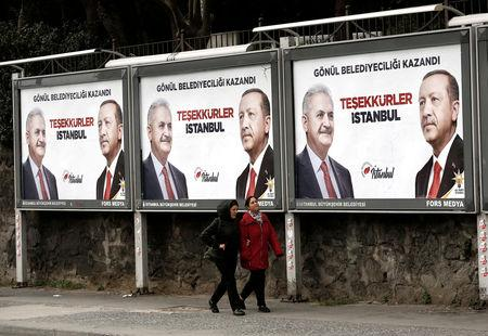 FILE PHOTO: People walk past by AK Party billboards with pictures of Turkish President Tayyip Erdogan and mayoral candidate Binali Yildirim in Istanbul, Turkey, April 1, 2019. REUTERS/Murad Sezer/File Photo