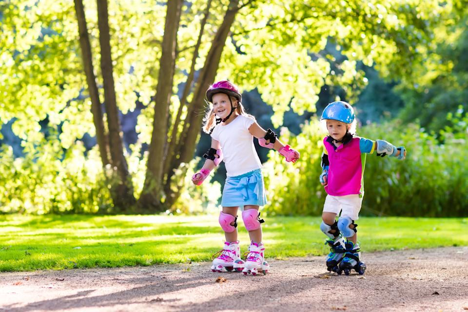 Girl and boy learn to roller skate in summer park. Children wearing protection pads and safety helmet for safe roller skating ride. Active outdoor sport for kids. Siblings help and support each other