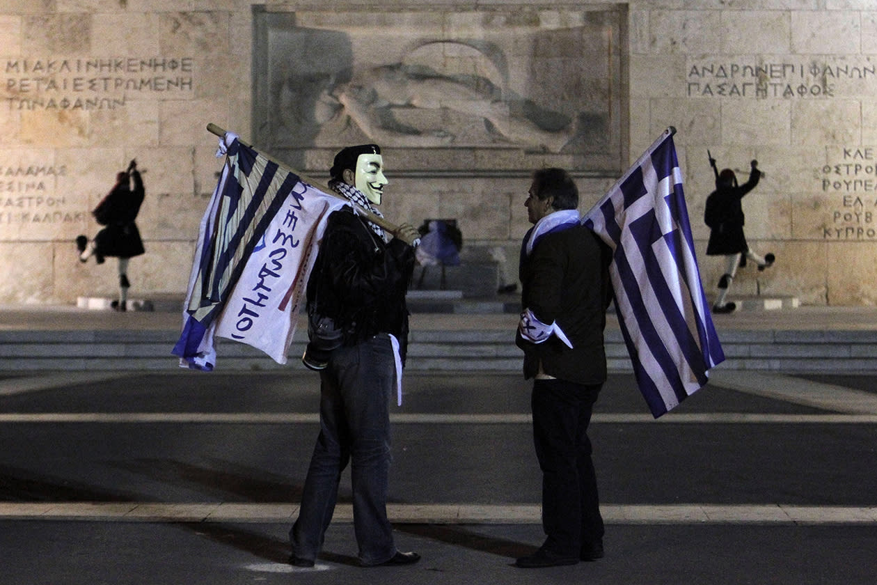 Supporters from the Independent Greeks party hold Greek flags as Presidential guards performs the changing of the guards ceremony outside the Greek parliament during an anti- austerity rally in central Athens.