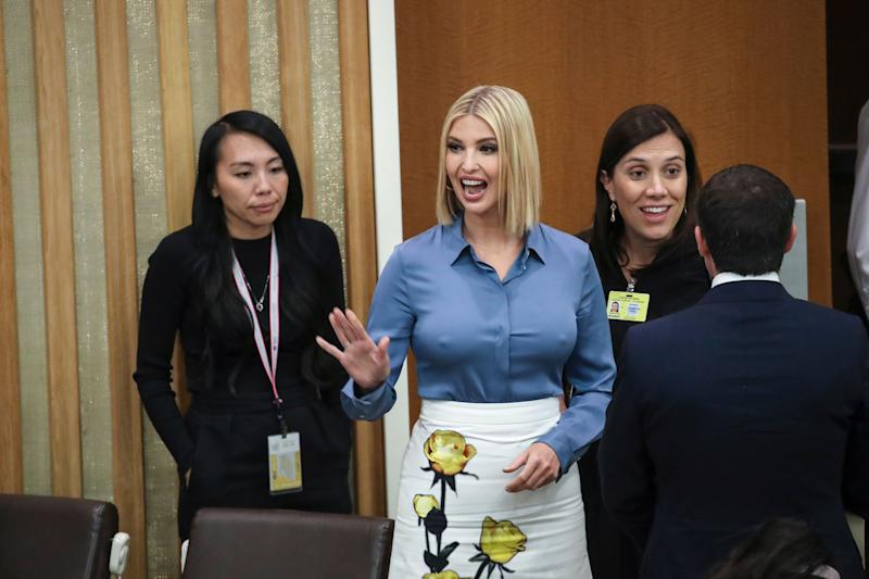 Ivanka Trump looks amazing in this blue T-shirt and white skirt with flowered design as she waves at someone in the background.