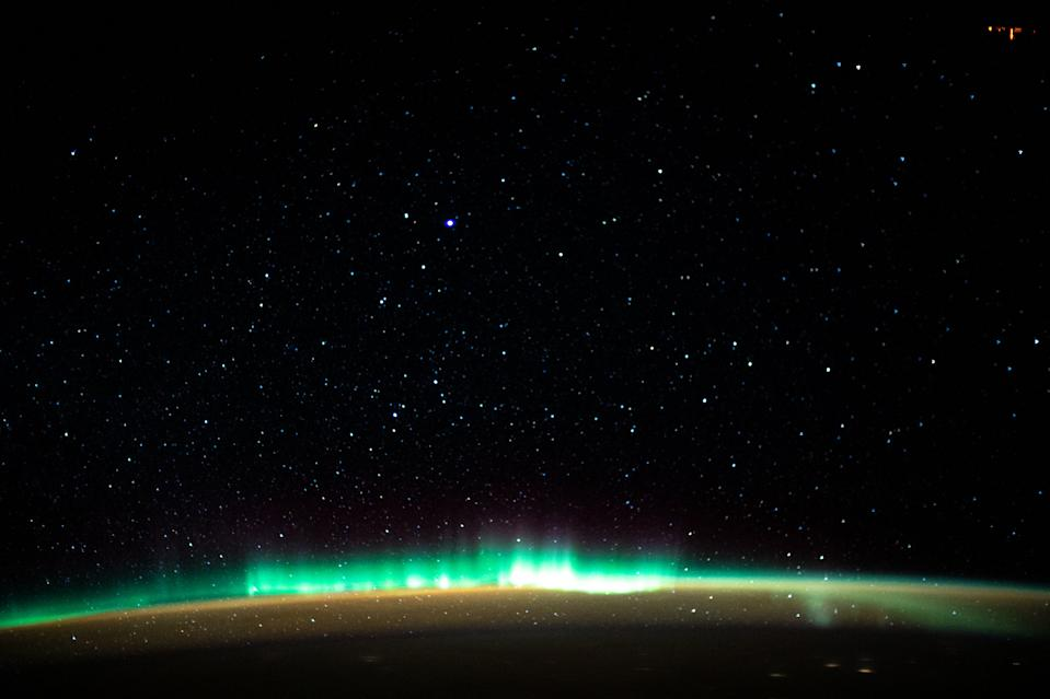 A vibrant, green aurora lights up Earth's upper atmosphere in this photo captured by an astronaut at the International Space Station. When this photo was taken on Jan. 22, the station was orbiting 261 miles (420 kilometers) above the Atlantic Ocean off the coast of North America. Beneath the northern lights is a blanket of marmalade-colored airglow, a type of luminescence caused by ultraviolet light that triggers chemical reactions high in Earth's atmosphere. Auroras, on the other hand, are created when charged particles from the sun ionize or excite particles in the atmosphere.