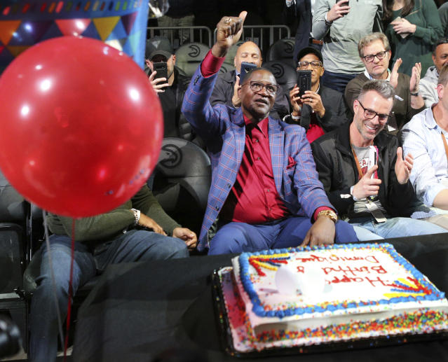 Dominique Wilkins gives the thumbs up as the Atlanta Hawks present the former player with a cake for his 60th birthday during the NBA basketball game against the Phoenix Sun Tuesday, Jan. 14, 2020, in Atlanta. (Curtis Compton/Atlanta Journal-Constitution via AP)
