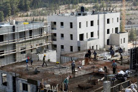 FILE PHOTO: Labourers work at a construction site in the Israeli settlement of Ramot in an area of the occupied West Bank that Israel annexed to Jerusalem
