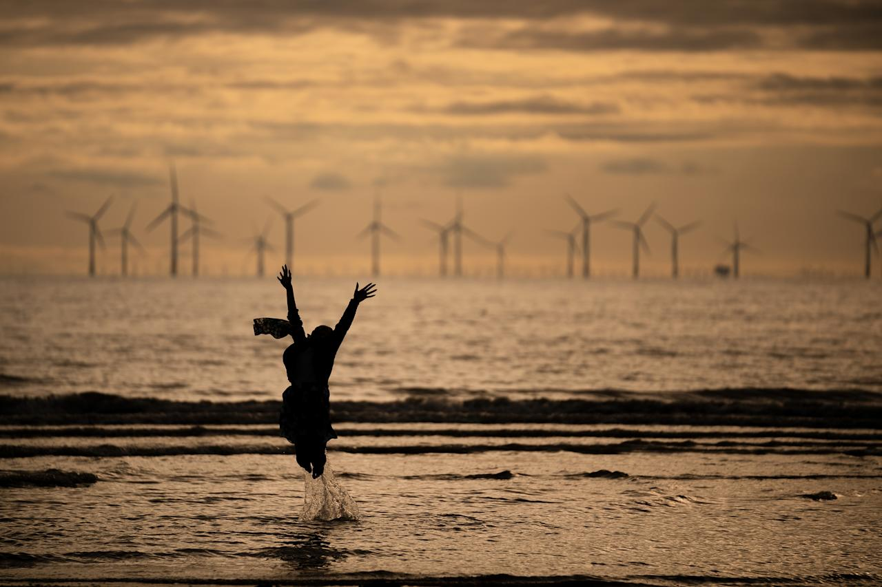 <p>A young girl dances and runs in the sea as she and her family celebrate Eid Al-Adha by watching the sunset at Crosby beach on August 21, 2018 in Liverpool, England. The traditional four-day celebratory festival marks one of the holiest days in the Islamic religious calendar. (Photo by Christopher Furlong/Getty Images) </p>