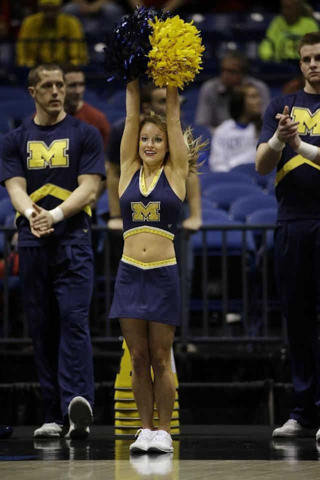 Michigan cheerleaders perform before an NCAA Midwest Regional semifinal college basketball tournament game between the Michigan and the Tennessee Friday, March 28, 2014, in Indianapolis. (AP Photo/David J. Phillip)