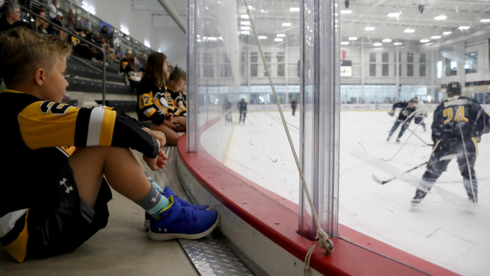 FILE - In this Sept. 13, 2019, file photo, nine-year-old Matt Manning, left, of Erie, Pa., sits with other young Pittsburgh Penguins hockey fans on the team's first day of training camp in Cranberry Township, Butler County, Pa. The most aggressive timetable, a person familiar with discussions told The Associated Press, would have players returning to their home rinks as early as May 15, followed by a training camp and possible exhibition games in June. (AP Photo/Keith Srakocic, File)
