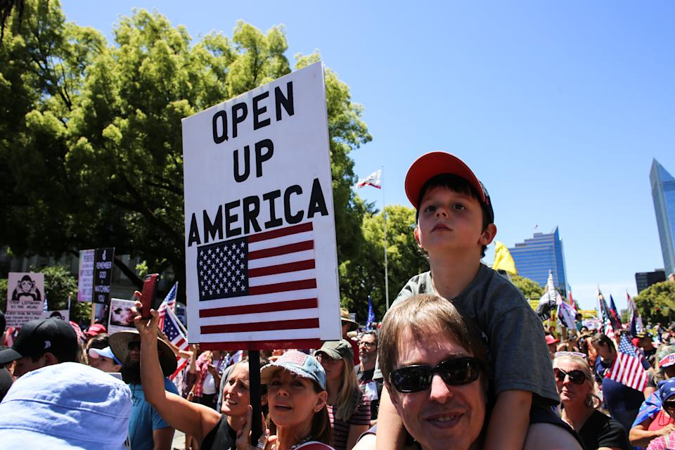 SACRAMENTO, CALIFORNIA, UNITED STATES - 2020/05/23: A protester holds a placard that says Wake Up America during the demonstration. Protesters gathered outside the California State Capitol to protest the California Stay-At-Home Orders and to call for the reopening of the California economy. (Photo by Stanton Sharpe/SOPA Images/LightRocket via Getty Images)