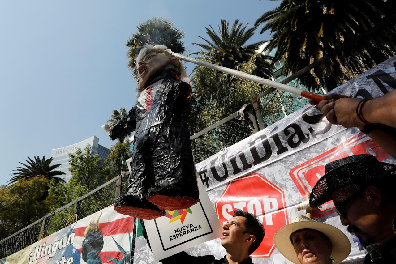 Activists hold a pinata resembling U.S. President Donald Trump as they mark one year anniversary of Trump's inauguration with a protest outside the U.S embassy in Mexico City, Mexico January 20, 2018. REUTERS/Carlos Jasso