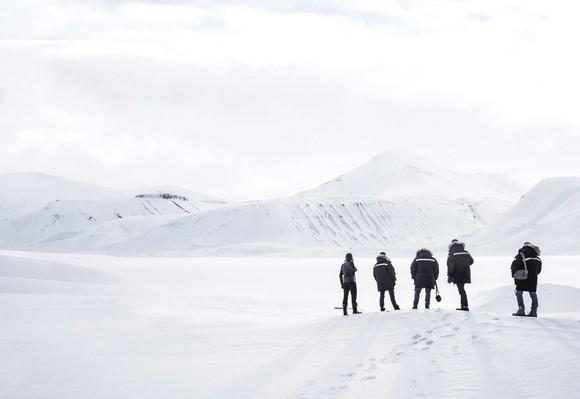 Five people on an icefield wearing heavy coats.