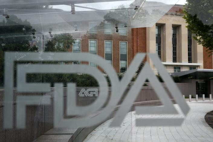 A view of a pane of glass with the FDA logo on it with the FDA building in the background