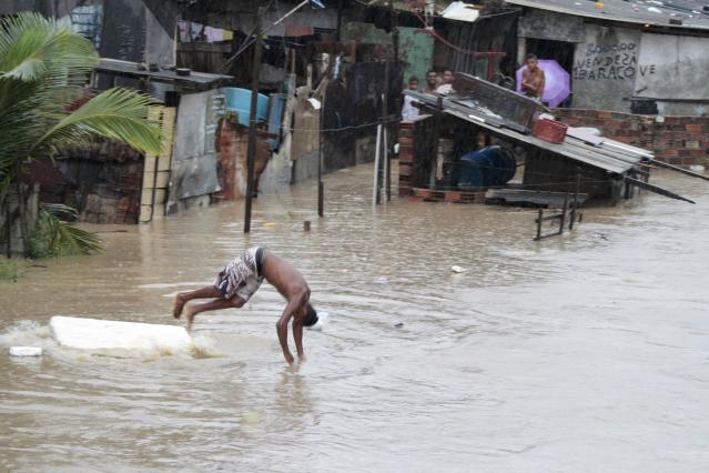 A boy jumps into floodwaters in the village of Novo Caxanga in Recife before the start of the 2014 World Cup Group G soccer match between U.S and Germany June 26, 2014 . REUTERS/Bobby Fabisak/JC Imagem (BRAZIL - Tags: SPORT SOCCER WORLD CUP ENVIRONMENT) FOR EDITORIAL USE ONLY. NOT FOR SALE FOR MARKETING OR ADVERTISING CAMPAIGNS. ATTENTION EDITORS - THIS PICTURE WAS PROVIDED BY A THIRD PARTY. THIS PICTURE IS DISTRIBUTED EXACTLY AS RECEIVED BY REUTERS, AS A SERVICE TO CLIENTS. FOR EDITORIAL USE ONLY. NOT FOR SALE FOR MARKETING OR ADVERTISING CAMPAIGNS.