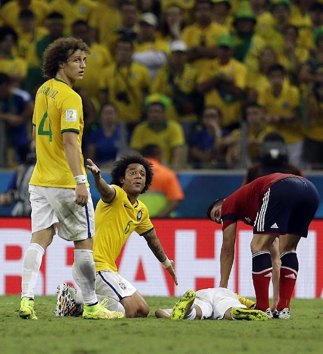 Brazil's Marcelo calls to the referee with David Luiz (4) as Neymar lies on the ground after being injured during the World Cup quarterfinal soccer match between Brazil and Colombia at the Arena Castelao in Fortaleza, Brazil, Friday, July 4, 2014. Brazil defeated Colombia 2-1 to advance to the semifinals. (AP Photo/Natacha Pisarenko)