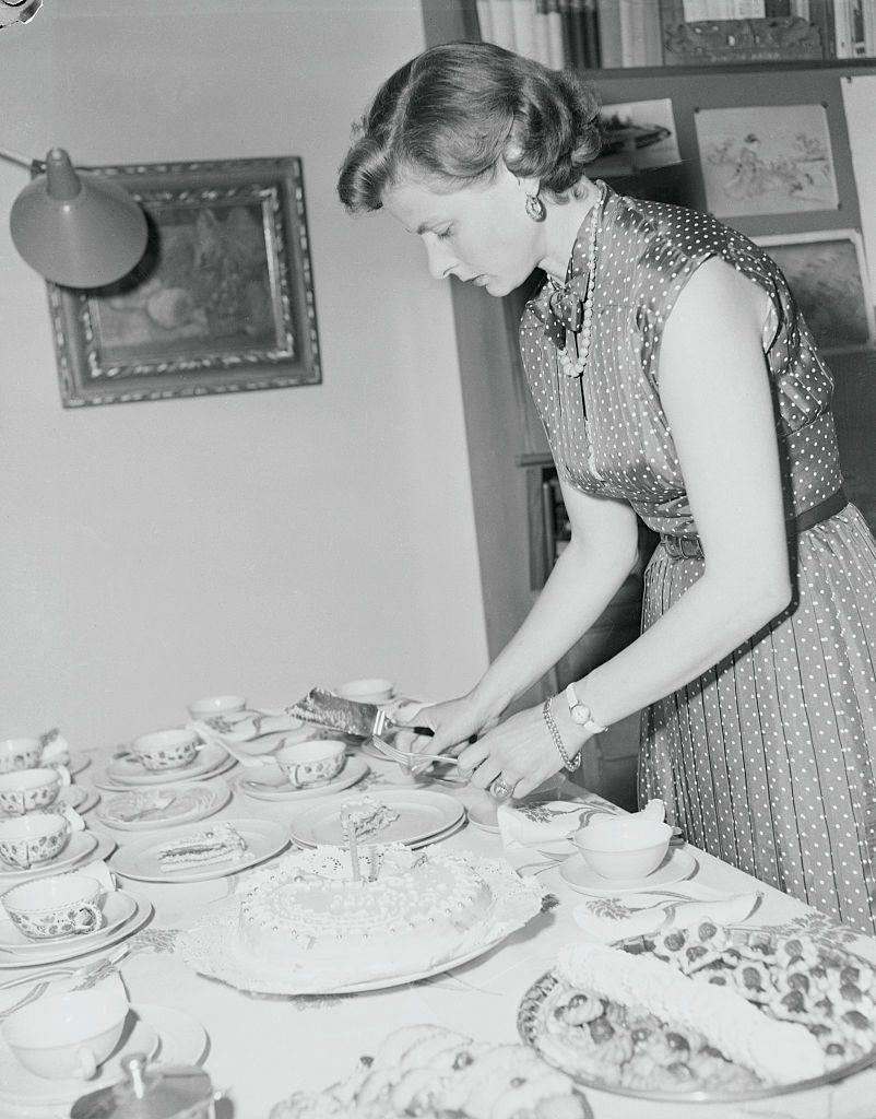 <p>The <em>Casablanca </em>star sets the table before entertaining family and friends for the first birthday of her twin daughters in 1953. </p>