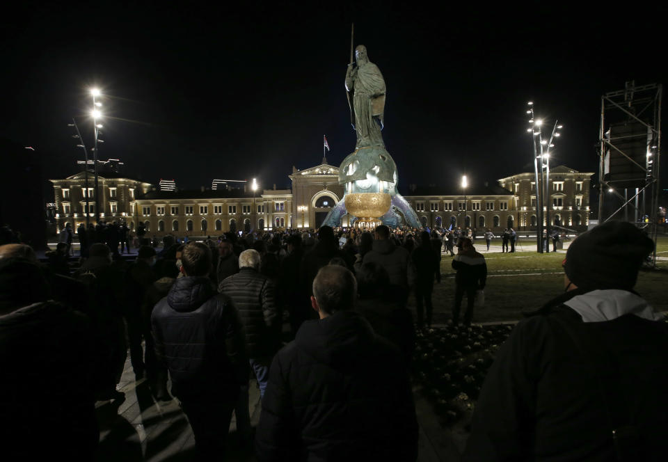 People walk around a 23-meter-high, 70-ton bronze sculpture of the legendary founder of the Serbian state, Stefan Nemanja, during the unveiling ceremony in Belgrade, Serbia, Wednesday, Jan. 27, 2021. President Aleksandar Vucic's allies say the bronze sculpture of Stefan Nemanja will be a new landmark of the Serbian capital. Opponents think the monument is a megalomaniac and pricy token of Vucic's populist and autocratic rule that should be removed. (AP Photo/Darko Vojinovic)