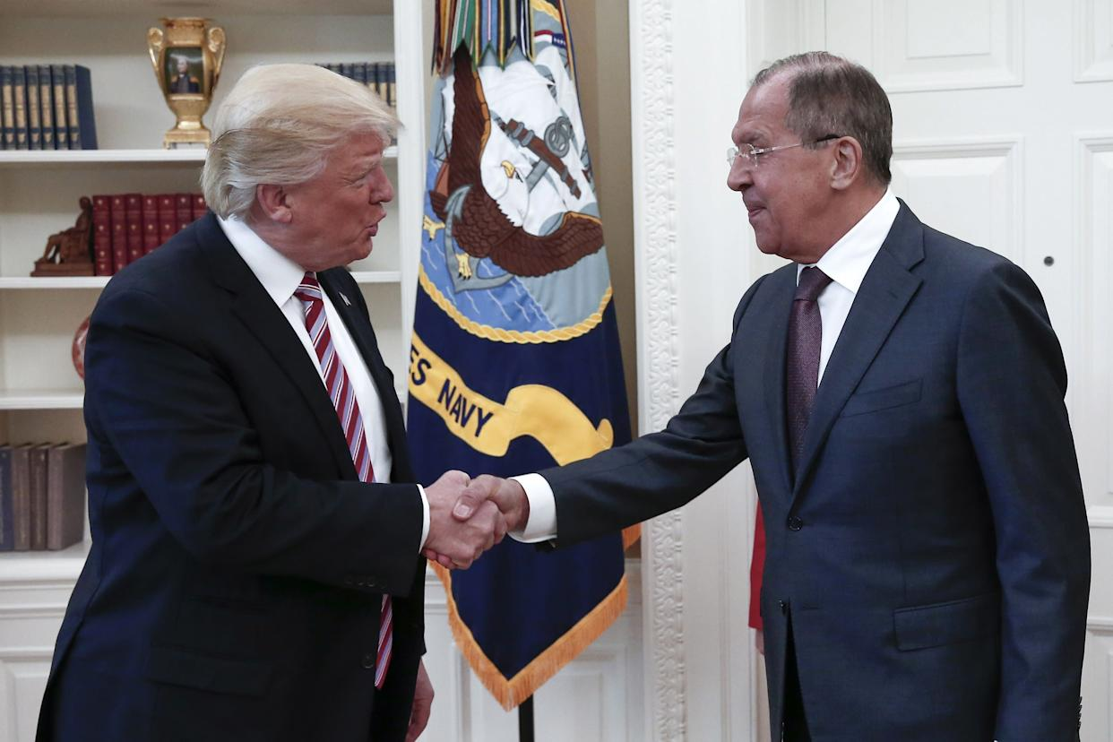 President Donald Trump shakes hands with Russia's Foreign Minister Sergei Lavrov as they meet for talks in the Oval Office.
