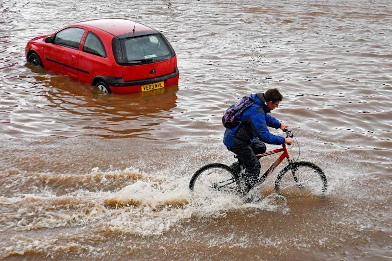 A man cycles past a stranded car on a flooded road in Birmingham city centre. The Met Office has issued a yellow weather warning for much of England and Wales today, with flooding expected in some areas.