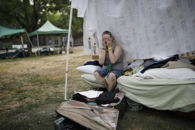 <p>Starla Davis cries as she packs a suitcase in her makeshift tent at an evacuation center Thursday, Aug. 9, 2018, in Redding, Calif. (Photo: John Locher/AP) </p>