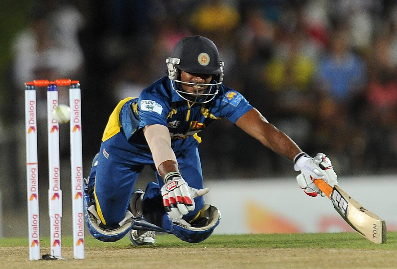 Sri Lankan batsman Kusal Perera dives and avoids a run out during the second Twenty20 cricket match between Sri Lanka and South Africa at the Suriyawewa Mahinda Rajapakse International Cricket Stadium in the southern district of Hambantota on August 4,2013. AFP PHOTO / LAKRUWAN WANNIARACHCHI