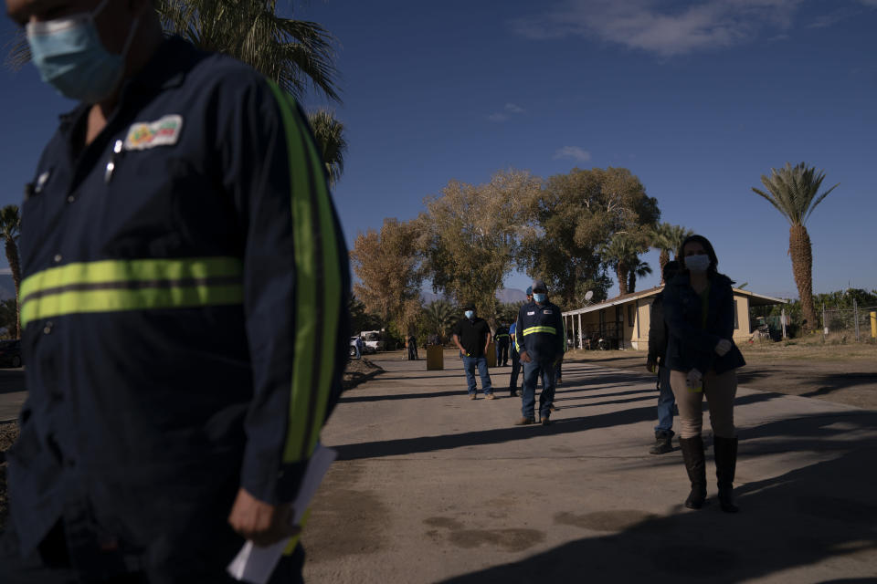FILE - In this Jan. 21, 2021, file photo, Hispanic farm workers wait in line to receive the Pfizer COVID-19 vaccine in Mecca, Calif. In some California counties, vaccination drives are targeting farmworkers. (AP Photo/Jae C. Hong, File)