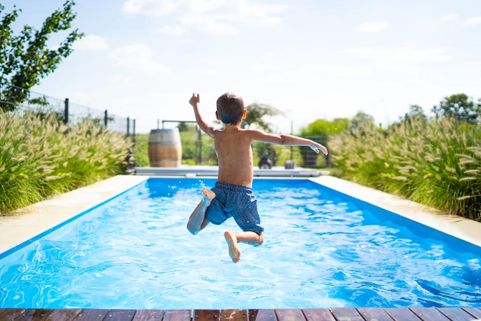 rear view of 4 year old boy jumping into private pool on sunny vacation day - boy is unrecognizable so can be used anonymous summer fun series