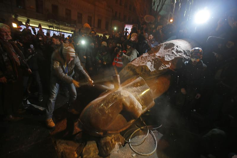 An anti-government protester smashes the statue of Vladimir Lenin with a sledgehammer in Kiev, Ukraine, Sunday, Dec. 8, 2013. Anti-government protesters have toppled the state of Bolshevik leader Vladimir Lenin in central Kiev amid huge protests gripping Ukraine. The chaotic protest further raised tensions in the Ukrainian capital. (AP Photo/Sergei Grits)
