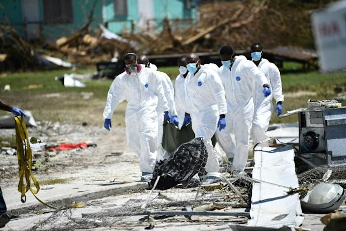 A removal team carries a victim in a body bag on Great Abaco island in the Bahamas (AFP Photo/Brendan Smialowski)