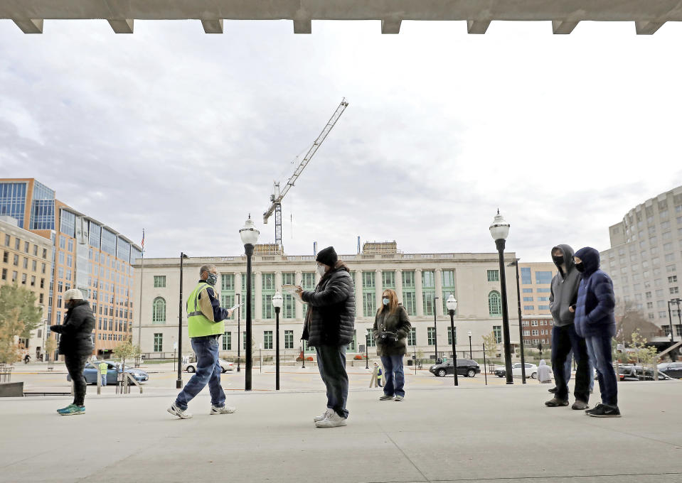 Voters participating in the first day of Wisconsin's in-person absentee voting window for the Nov. 3 election wait in line outside the city's City-County Building in Madison, Wis., Tuesday, Oct. 20, 2020. (John Hart/Wisconsin State Journal via AP)