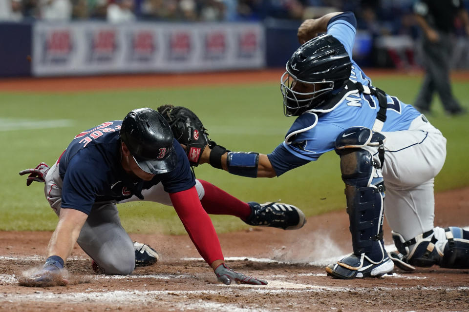 Tampa Bay Rays catcher Francisco Mejia (28) tags out Boston Red Sox's Hunter Renfroe (10) at home while trying to score on a single by Christian Vazquez during the seventh inning of a baseball game Thursday, June 24, 2021, in St. Petersburg, Fla. (AP Photo/Chris O'Meara)