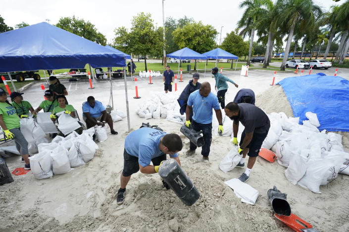 City workers fill sandbags at a drive-thru sandbag distribution event for residents ahead of the arrival of rains associated with tropical depression Fred on Aug. 13, 2021, at Grapeland Park in Miami. (Wilfredo Lee / AP)