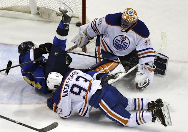 St. Louis Blues' Vladimir Sobotka, of the Czech Republic, is upended by Edmonton Oilers' Ryan Nugent-Hopkins (93) after scoring past Edmonton Oilers goalie Ben Scrivens, top right, during the first period of an NHL hockey game Thursday, March 13, 2014, in St. Louis. (AP Photo/Jeff Roberson)