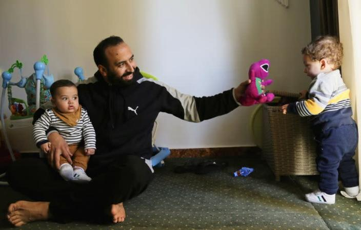 Mohamed Abdallah holds his biological son Soliman as he plays with Dawood, an orphan he sponsors, in their home in Cairo