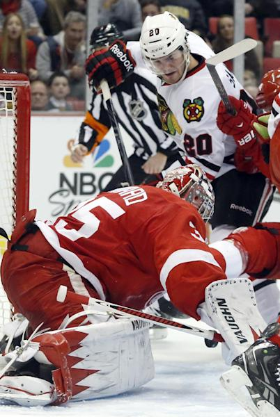 Chicago Blackhawks left wing Brandon Saad (20) tries to get a shot against Detroit Red Wings goalie Jimmy Howard (35) in the second period of an NHL hockey game on Sunday, March 3, 2013, in Detroit. (AP Photo/Duane Burleson)