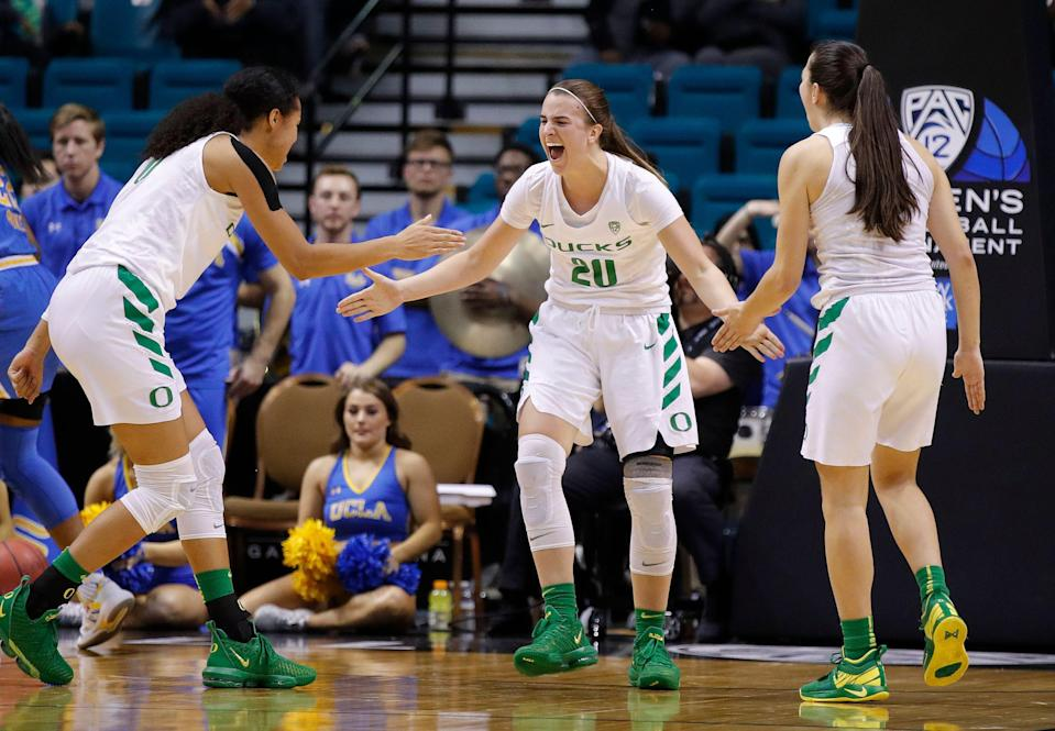Oregon's Satou Sabally, Sabrina Ionescu, and Maite Cazorla, from left, celebrate as the team led UCLA with seconds left in overtime in an NCAA college basketball game in the semifinals of the Pac-12 women's tournament Saturday, March 9, 2019, in Las Vegas. (AP Photo/John Locher)