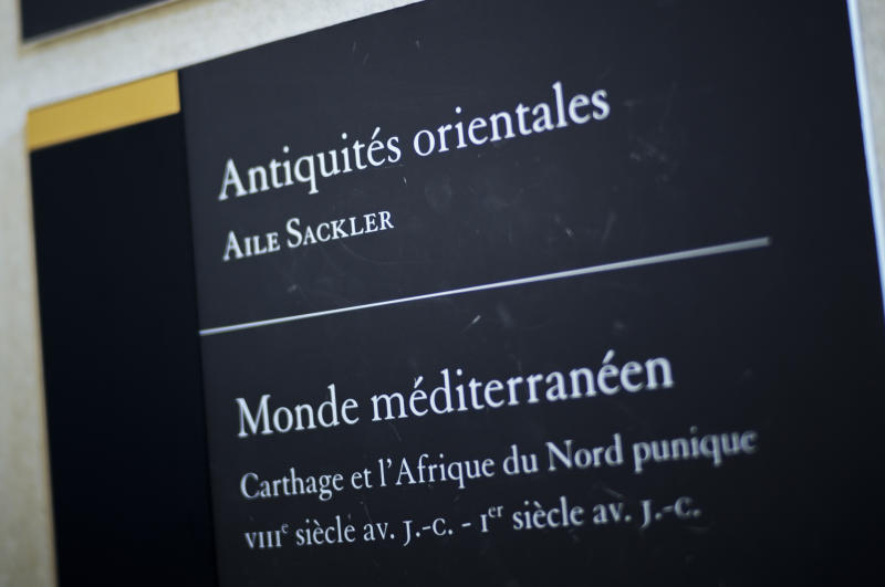 """A sign reads """"Oriental Antiquities, Sackler wing"""" at the Louvre Museum in Paris, France, Wednesday, July 17, 2019. France's Louvre museum has taped over the Sackler name as donors to a wing of the building after protests against the family blamed for the opioid crisis in the United States. (AP Photo/Kamil Zihnioglu)"""