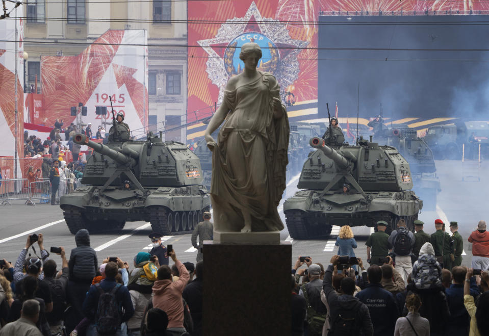 People take photos as self-propelled artillery vehicles Msta-S travel during a rehearsal for a military parade at Dvortsovaya (Palace) Square in St.Petersburg, Russia, Saturday, June 20, 2020. The military parade marking the 75th anniversary of the Nazi defeat was postponed from May 9 due to the outbreak of the coronavirus pandemic and is now set to take place on June 24.(AP Photo/Dmitri Lovetsky)