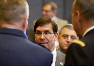 U.S. Secretary for Defense Mark Esper, center, speaks with military representatives as he attends a meeting of the North Atlantic Council at NATO headquarters in Brussels, Thursday, Feb. 13, 2020. NATO ministers, in a second day of meetings, will discuss building stability in the Middle East, the Alliance's support for Afghanistan and challenges posed by Russia's missile systems. (AP Photo/Virginia Mayo)