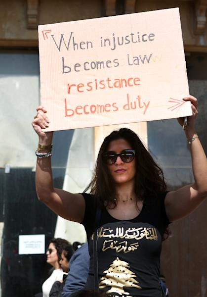 A Lebanese woman holds a placard during a protest in downtown Beirut on March 19, 2017, against increased taxes (AFP Photo/PATRICK BAZ)