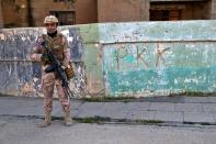 Iraqi army soldier stands next to the graffiti left by an affiliate of the Kurdistan Worker's Party, or PKK, which recently withdrew in Sinjar, Iraq. Friday Dec. 4, 2020. A new agreement aims to bring order to Iraq's northern region of Sinjar, home to the Yazidi religious minority brutalized by the Islamic State group. Since IS's fall, a tangled web of militia forces have run the area, near the Syrian border. Now their flags are coming down, and the Iraqi military has deployed in Sinjar for the first time in nearly 20 years. (AP Photo: Samya Kullab)