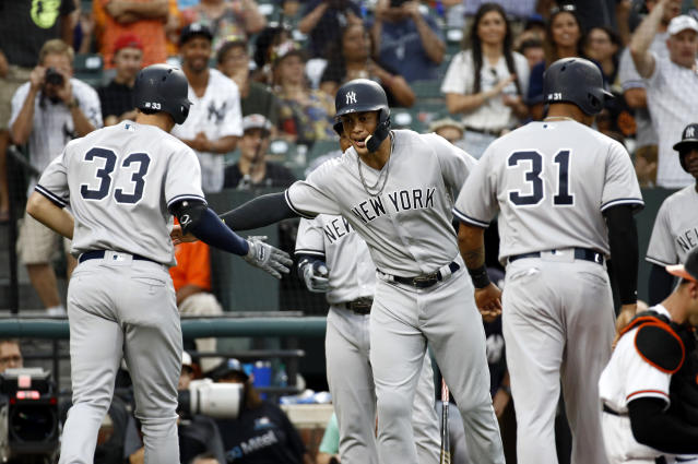 New York Yankees' Giancarlo Stanton, center, greets teammate Greg Bird after scoring on Bird's grand slam during the third inning against the Baltimore Orioles in a baseball game Wednesday, July 11, 2018, in Baltimore. (AP Photo/Patrick Semansky)