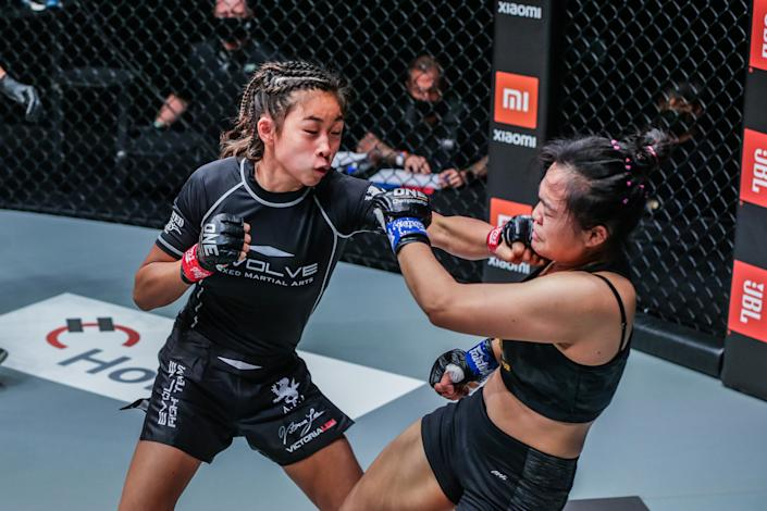 Victoria Lee (left) throws a blow at her Thai opponent Sunisa Srisen en route to winning her first professional MMA fight at ONE: Fists of Fury.  (PHOTO: ONE Championship)