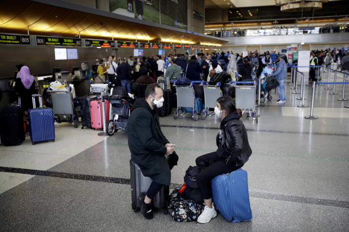 Image: People wait to check in their luggage at Los Angels International Airport on March 14, 2020. (Marcio Jose Sanchez / AP)