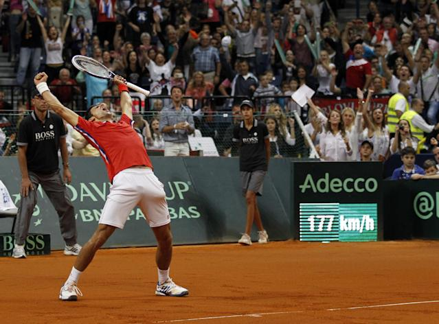 Novak Djokovic of Serbia shouts with joy as he wins his Davis Cup semifinal tennis match against Milos Raonic of Canada, in Belgrade, Serbia, Sunday, Sept. 15, 2013. (AP Photo/Darko Vojinovic)
