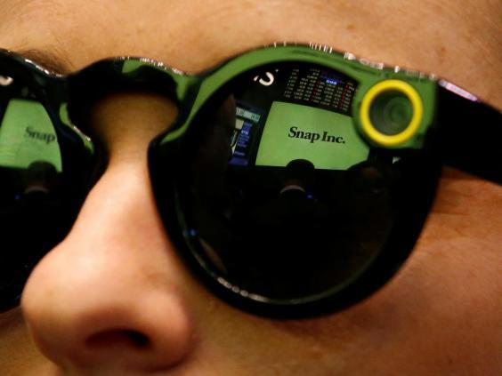 A woman wears Snapchat Spectacles on the floor of the New York Stock Exchange (NYSE) while waiting for Snap Inc. to list their IPO in New York, U.S., March 2, 2017 (REUTERS/Brendan McDermid)