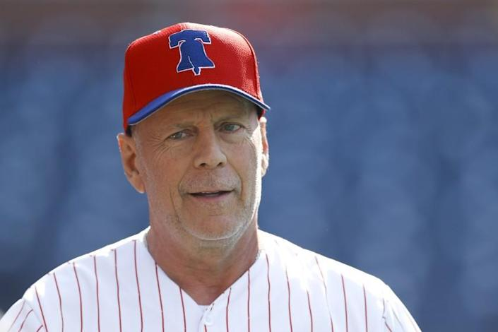 Actor Bruce Willis watches batting practice before a Philadelphia Phillies-Milwaukee Brewers game in May 20`19